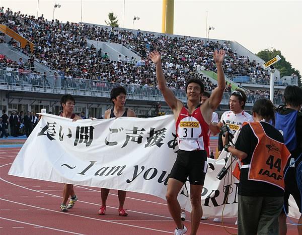 レース後、100mを走った選手とともに朝原は、競技場内を一周。観客の声援に応えた