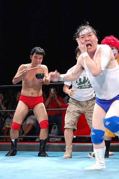 上島(右)扮する大仁田は奮闘するも、お約束おでん攻撃で自爆
