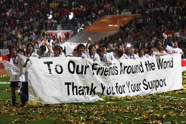 世界からの東日本大震災の復興支援への感謝が記されたバナーを持ってピッチを一周する選手たち