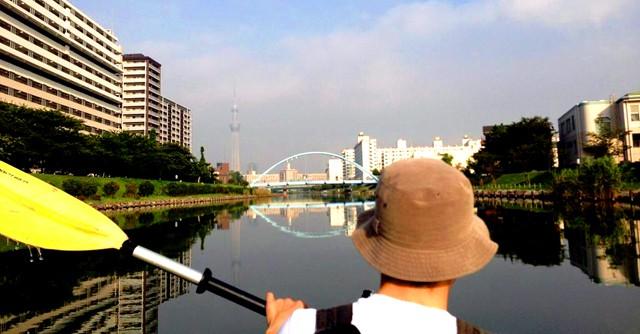 早朝から都会のど真ん中でカヌー。東京スカイツリー(写真左奥)を眺める