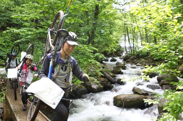 マウンテンバイクを担いで美しい渓流を渡る。少々きつくても気持ちよさそう。「エクストリームシリーズ2013尾瀬檜枝岐大会」で。