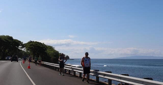 朝日が昇り、輝く海を眺めて走るランナーたち