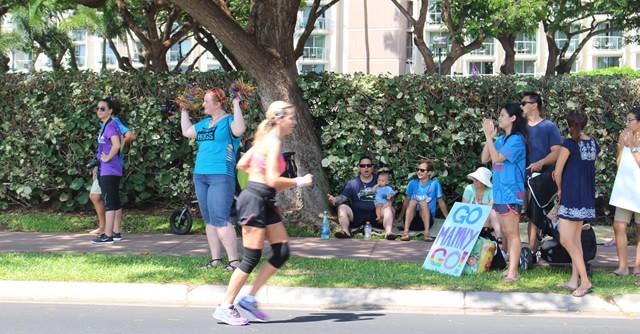 カラフルな応援グッズを手にする人々。ランナーにエール!