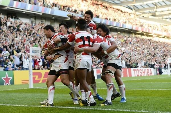 五郎丸(左)のトライに喜ぶ日本代表。南アフリカを破る快挙を成し遂げた