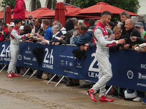 元F1ドライバーのルーカス・ディ・グラッシ(左)とアンドレ・ロッテラーがサインに出ると、ファンがドライバーの名前を呼んで、Tシャツ、旗、プログラムへとサインを求める。