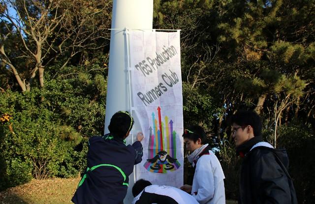 「アイマス」のキャラクターたちが所属する「765 Production」の名をプリントしたのぼり旗をセッティング