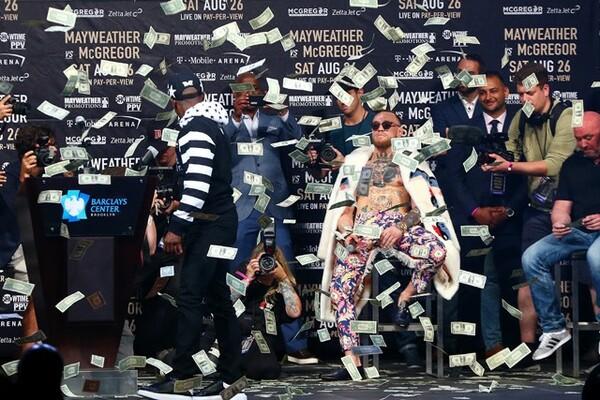 """""""金の亡者""""メイウェザー(左)は、壇上で1ドル札をばら撒くパフォーマンスも"""