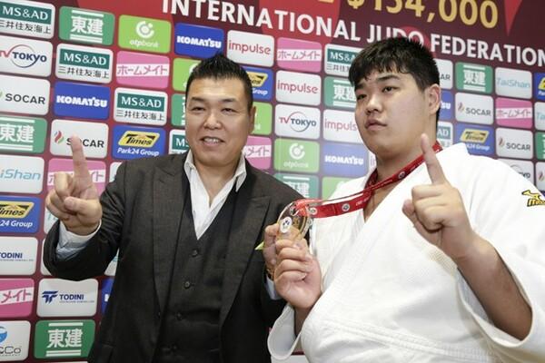 金メダルを手にしてポーズを取る小川雄勢(右)と父・直也