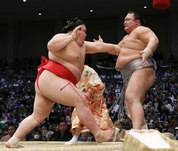北勝富士(右)を突き出す阿武咲。スマホで対戦相手を研究する