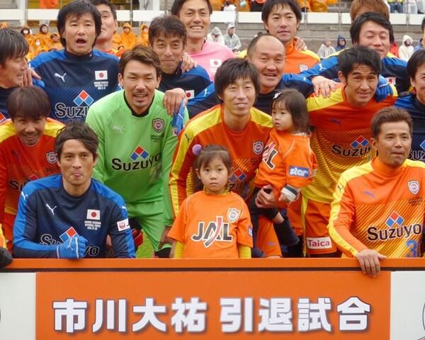 引退試合で子供を抱きながら記念写真に納まる元日本代表の市川大祐