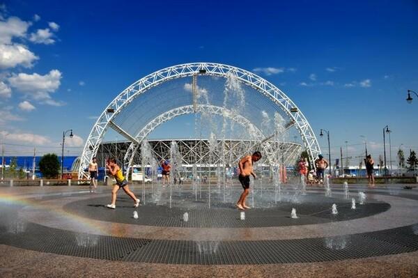 あまりの暑さに公園の噴水で水浴びする子供たち。遠景にボルゴグラード・アリーナが見える