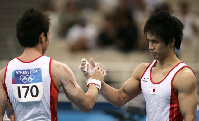 鉄棒の最終演技者であった冨田洋之(右)は、盟友・鹿島丈博からバトンを受け継いだ