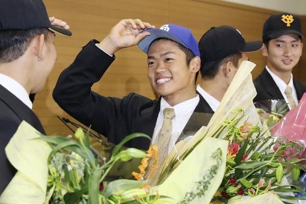 1位指名を受けた中日の帽子をかぶり、笑顔を見せる大阪桐蔭の根尾
