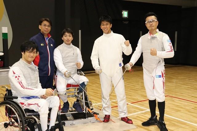車いすフェンシングの、白いユニホームに身を包む武井さんとパラアスリートたち(左から笹島貴明、加納慎太郎、武井さん、安直樹)