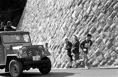 往路5区で伴走車からの監督の激励を受け山登りに挑む選手(1968年1月)