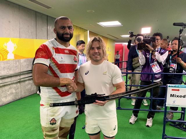 健闘を称え合い南アフリカ代表のファフ・デクラーク(前列右)に模造刀を贈呈した日本代表のリーチ・マイケル主将、ラグビーに根付くファミリー文化の表れだ