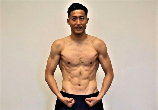 ローパワーを重視するサッカー選手らしい引き締まった肉体の都倉。バロテッリポーズをすると広背筋や腸腰筋のすごさが際立つ