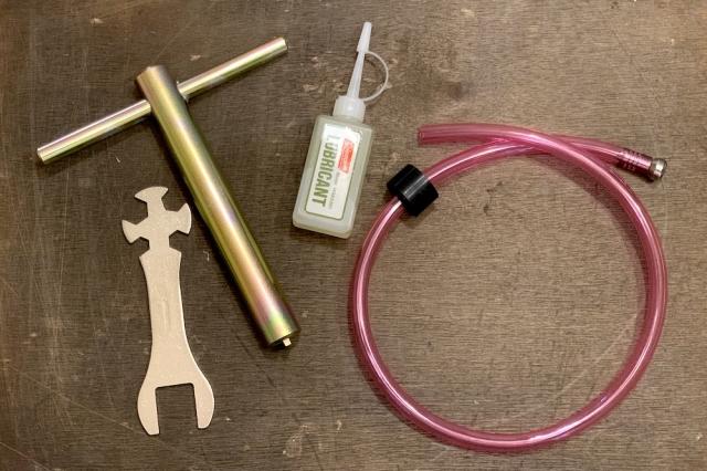(左から)チェックバルブレンチ、スーパーレンチ、リュブリカント(ポンプカップ専用潤滑油)、残ガソリン抜き取りポンプ。