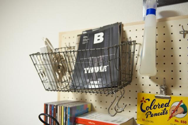 有孔ボードフックをふたつ使い、メタルバスケットをぶら下げた小物入れ。本が数冊入るものを選んでおくと便利。