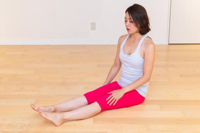 床に座る。呼吸のときと同様、骨のでっぱりを意識して。あればヨガマットのうえでもOK! 背筋をしっかり伸ばして。