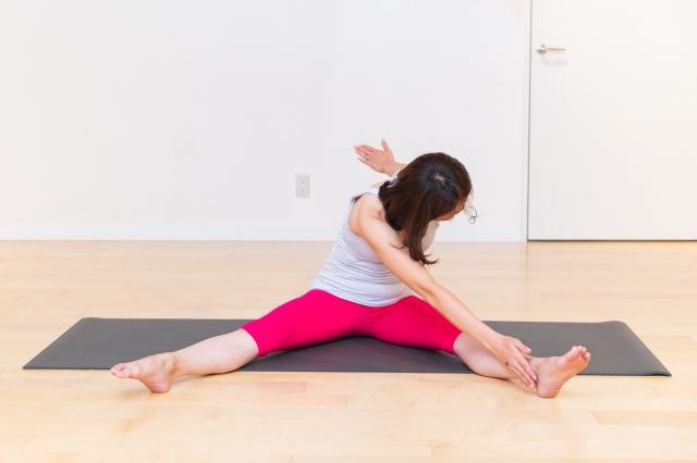 ゆっくりと前屈し、右手を左足の内側にタッチ