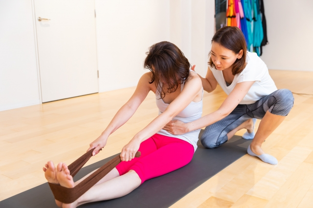 足裏にトレーニングバンドを引っ掛ける。足の裏だけでなく、背中を伸ばし、おへそを背中側に押し込むようにしてお腹をへこませる。