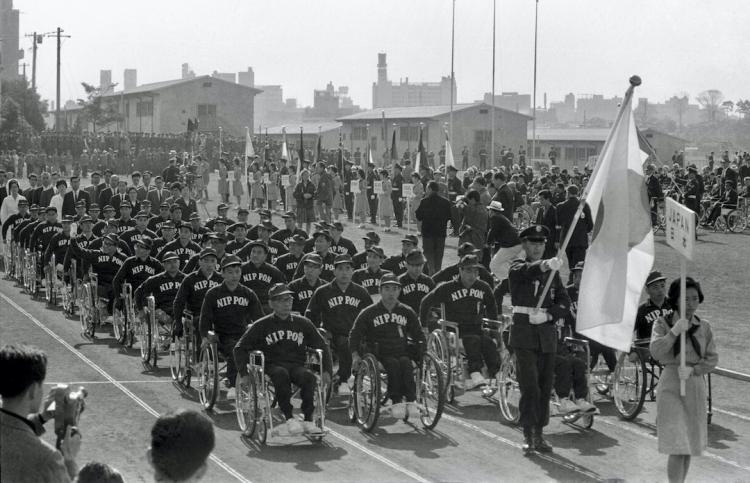 1964年の東京パラリンピック開会式で、車いすで入場行進する日本選手団=東京・代々木の選手村