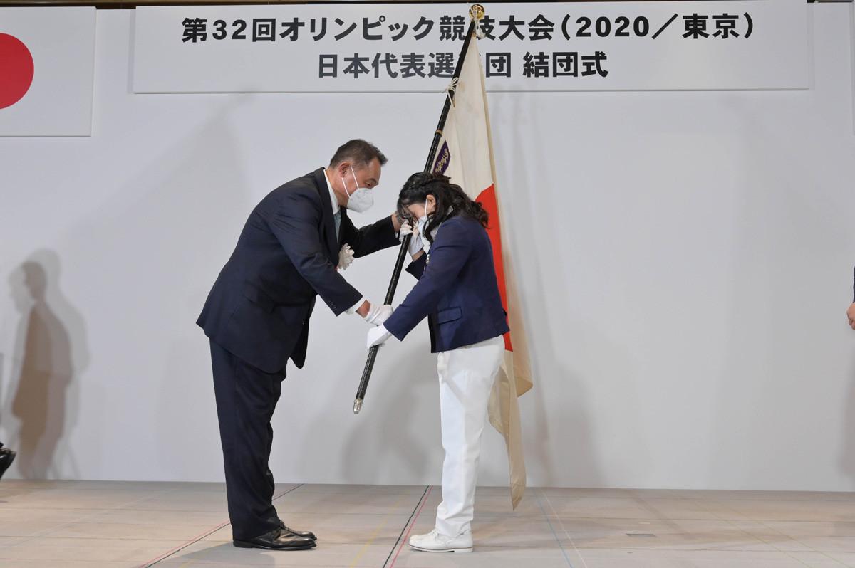 山下JOC会長(写真左)から国旗を受け取った旗手の須崎