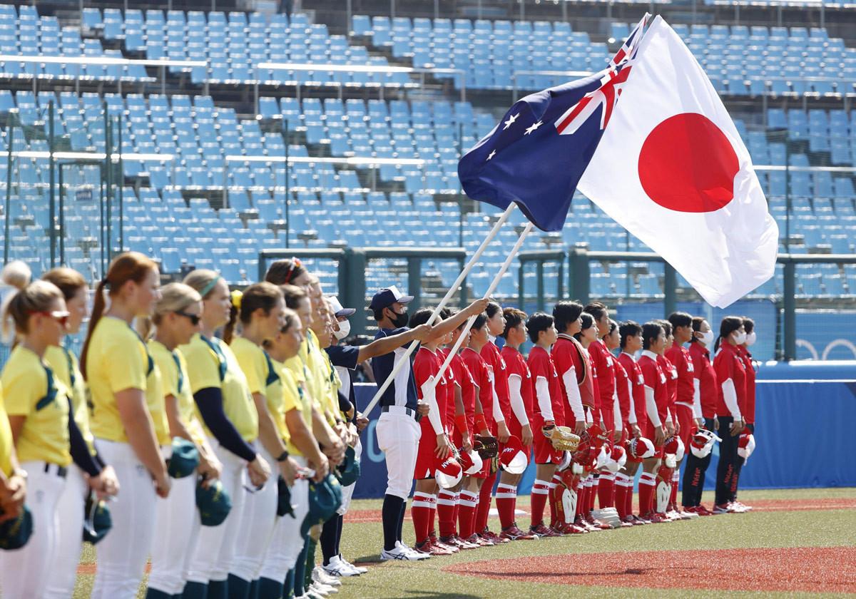 東京五輪のソフトボール開幕戦を前に整列する日本(奥)とオーストラリアの選手=21日午前、福島県営あづま球場