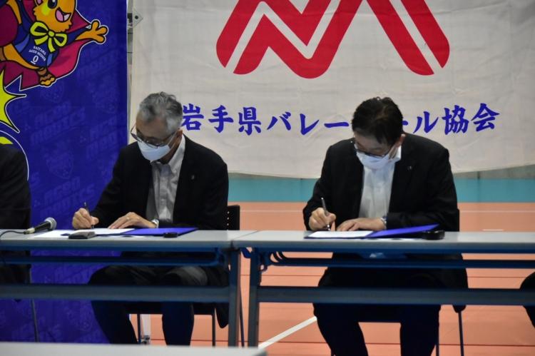 締結書にサインする岩手県バレーボール協会の山形会長(左)と埼玉上尾メディックスの中島部長(右)